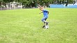 Boy plays soccer on a football field with natural grass.