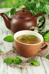 Teapot and cup of herbal tea with fresh mint flowers