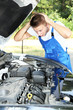 Young auto mechanic repairing car engine outdoors