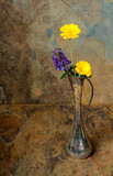 Purple and yellow wildflowers in an antique silver vase on a sla