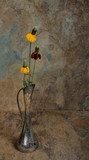 Wild flowers in an antique silver vase with a slate background