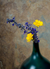 Blue and yelow wildflowers in a turquoise vase against a rustic