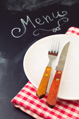 Plate, knife and fork on tablecloth over blackboard background