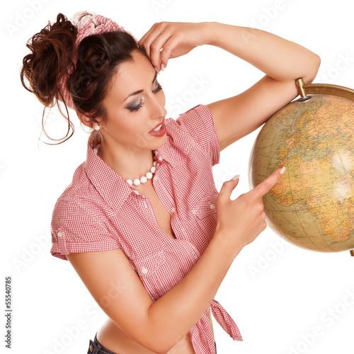 hübsche Frau zeigt auf Weltkugel