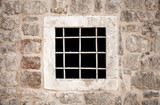 Ancient stone prison wall with metal window bars