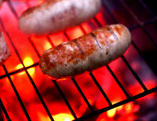 Juicy grilled sausages on a flaming grill.