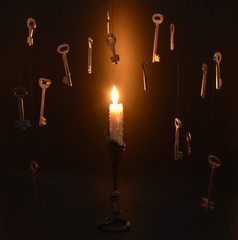 Burning candle with hanging keys