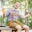 junger Mann mit Bier und Brezen