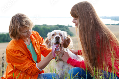 mother and her daughter with dog (Irish setter) outdoors