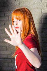 Attractive red haired young girl doing stop sign with her hand