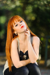 Attractive red haired young girl sitting and touching her neck