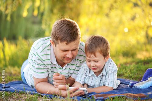 Father and son playing with smartphone