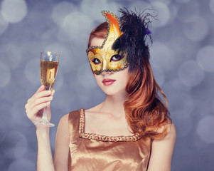 Redhead women in mask with champagne