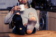 Man with worn out socks having coffee in kitchen - 55553136