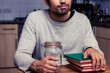 Man with jam jar and stack of books