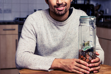 Happy man sitting in kitchen with piggy bank