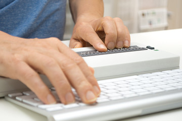 Blind person working on computer with braille display, keyboa