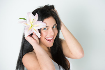 Pretty woman with healthy skin and pink lily