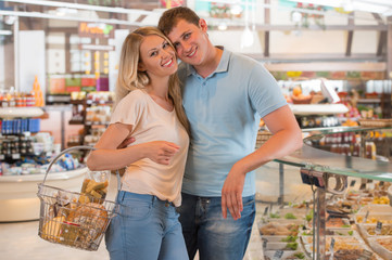 Young couple shopping at supermarket - filling cart