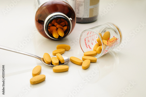 nutritional supplement (drug pills) in spoon and containers