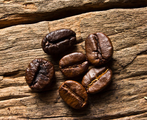 Fresh coffee beans in   on wood background