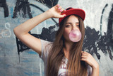 trendy model posing on graffiti. Blow bubblegum