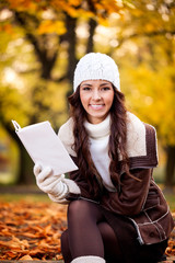 Smiling woman reading in the park
