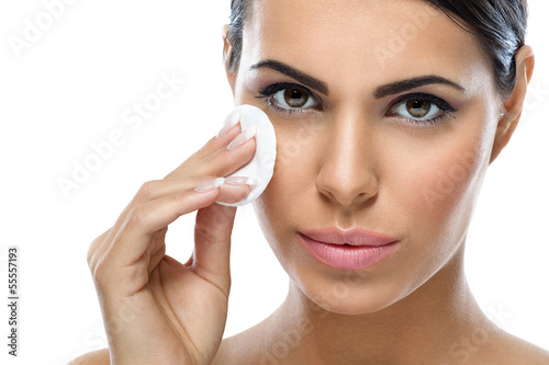 Young woman cleaning face with cotton pad