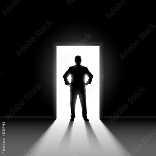 Silhouette of man standng in doorway.