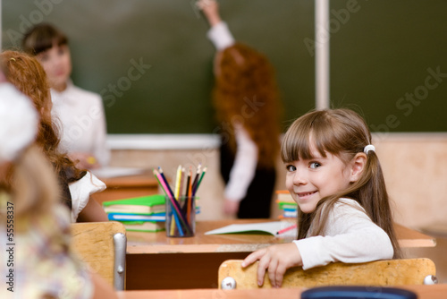 Portrait of schoolboy at workplace with teacher on background