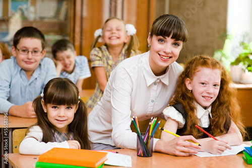 Portrait of diligent schoolgirl  at lesson surrounded by her cla