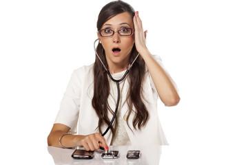 shocked female doctor examines phones using a stethoscope