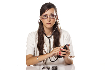 serious female doctor examines phones using a stethoscope