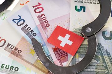 Euroscheine mit Handschellen und Schweizer Flagge