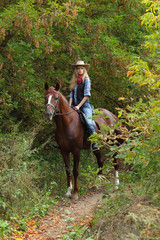 Cowgirl relaxing with horse in the forest