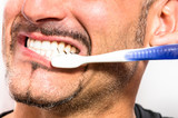 Young Man brushing white perfect Teeth with a Toothbrush