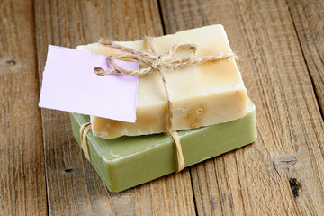 Two natural soap bars with tag on wooden background