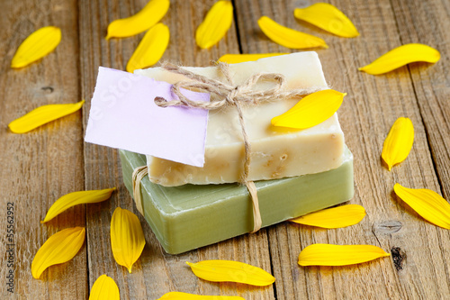 Natural soap bars with tag on wooden background