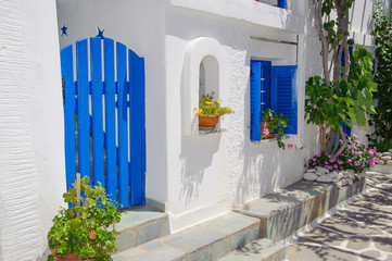 Greek traditional blue gate in white washed house