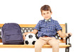 Smiling schoolboy sitting on a bench with school bag and footbal