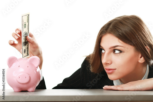 Young beautiful woman sitting with piggy bank (money box)