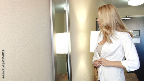 Business woman getting dressed in mirror