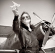 Young beautiful woman pilot in a airplane.