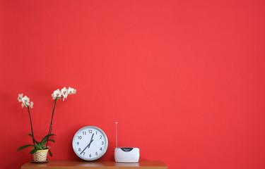 Parete rossa con orchidea e oggetti