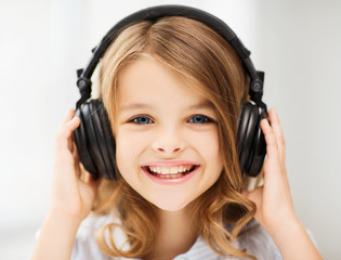 little girl with headphones at home