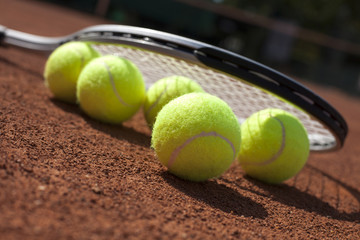 Tennis balls and racket on field