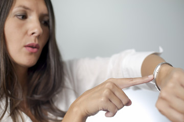 woman tapping on wrist watch