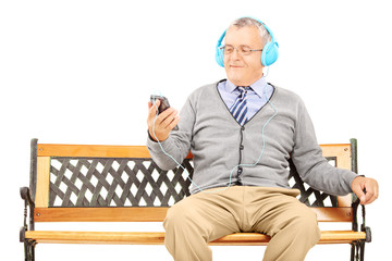 Gentleman sitting on a bench and listening music from his mobile
