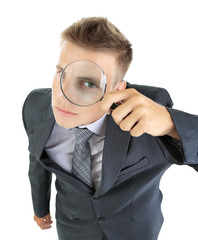 Young businessman looking through magnifying glass isolated