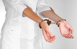 Doctor in handcuffs isolated on white